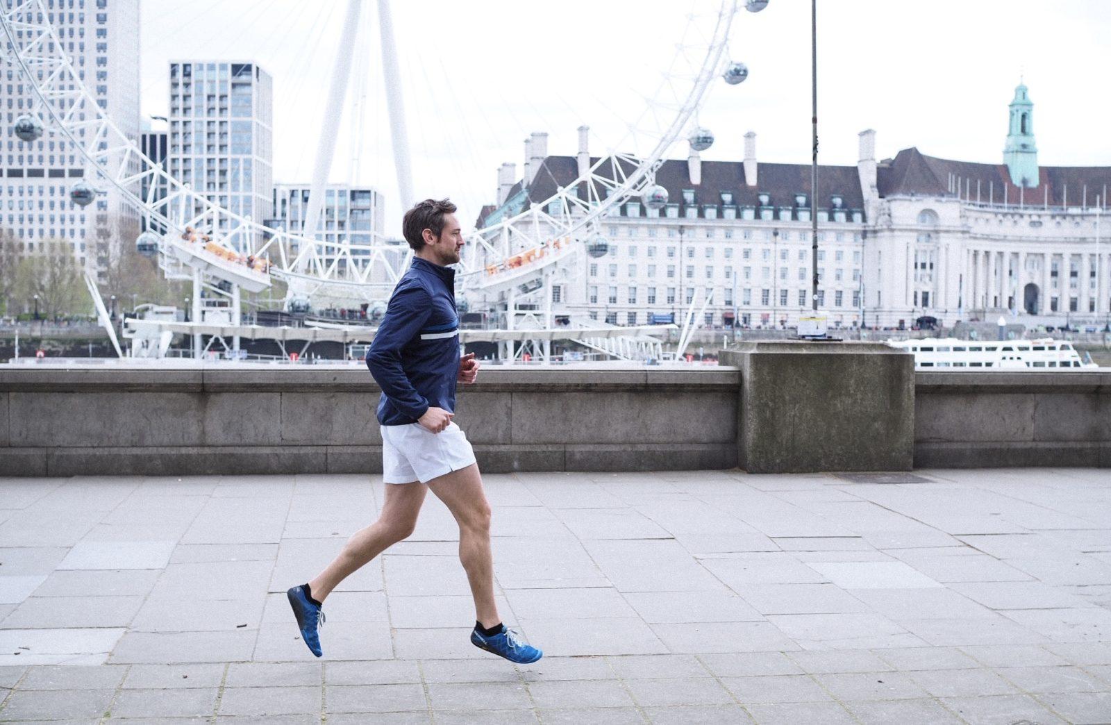 man running past london eye marathon